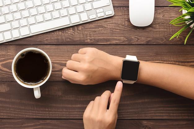 Main en utilisant smartwatch sur la vue de dessus de bureau