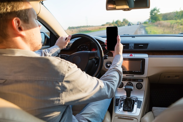 Main en utilisant le téléphone envoyant un texte en conduisant au travail