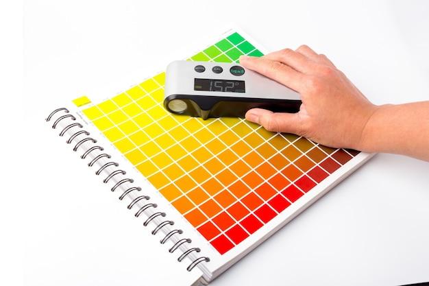 La main utilise un densitomètre. un densitomètre est un instrument utilisé pour mesurer la densité des couleurs. il est couramment utilisé dans l'industrie de l'imprimerie et de la conception graphique.