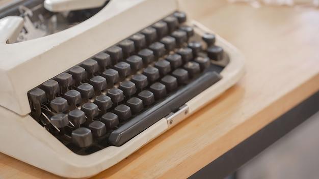 La main utilise des machines à écrire vintage sur la table en bois.