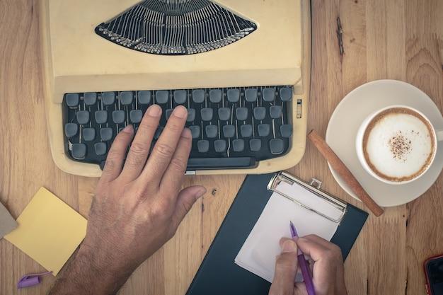 Main utilise des machines à écrire vintage sur une table en bois.