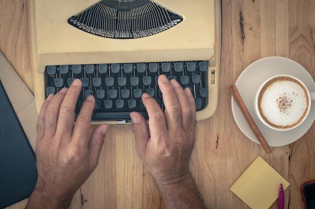 Main utilise des machines à écrire vintage sur table en bois