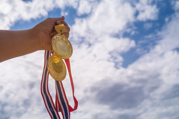 Main de vainqueur soulevée tenant deux médailles d'or avec un ruban thaï contre le ciel bleu.