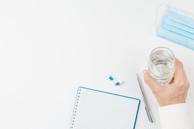 Main avec verre d'eau et fond blanc de pilule