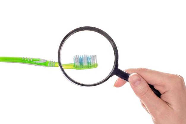 Main avec verre loupe et brosse à dents
