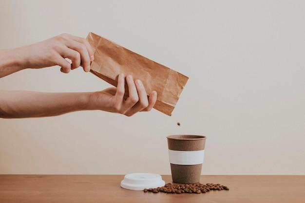 Main versant les grains de café d'un sac en papier dans une tasse à café
