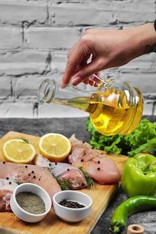 Main verse de l'huile dans une assiette de viandes de poulet crues avec un bouquet de légumes.