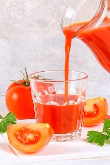 Main versé le jus de tomate d'un pichet dans un verre sur une table en béton gris.