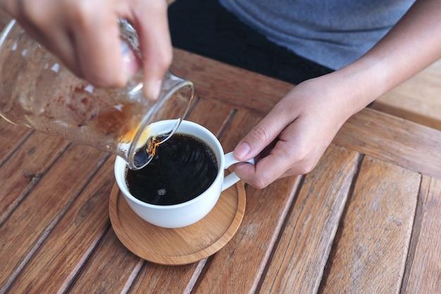 Main verser le café goutte à goutte dans une tasse blanche sur une table en bois vintage