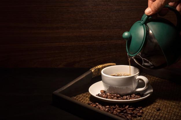 Main verser le café sur la tasse de café blanc avec des grains de café sur le plateau en bambou