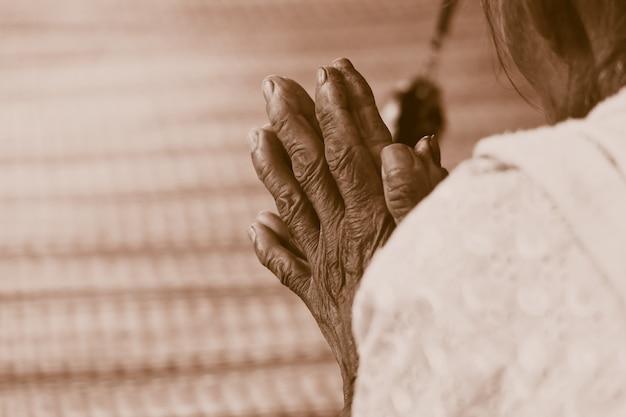 Main de vieille femme priant ton vintage rétro