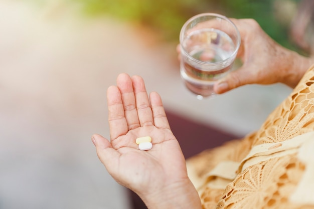 La main d'une vieille femme tient une pilule et un verre d'eau potable pour manger. concept de soins de santé.