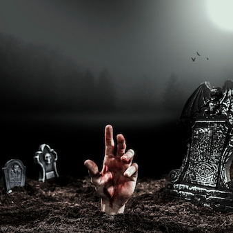 Main vivante dépassant de la tombe au clair de lune