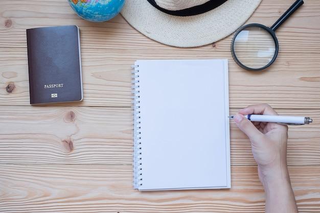 Main voyageur écrit sur cahier avec accessoires, appareil photo, passeport