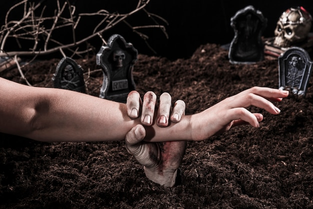 Main de zombie tenant le bras d'une personne au cimetière d'halloween