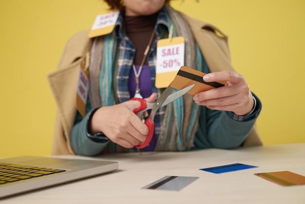 Mains d'une accro du shopping coupant ses cartes de crédit après avoir acheté trop de vêtements en vente