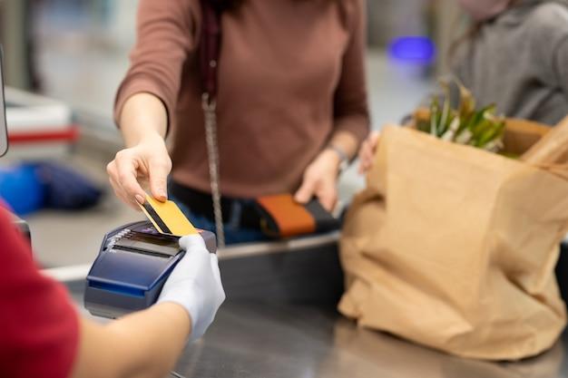 Les mains d'une acheteuse mature avec un smartphone sur une machine de paiement vont payer les produits alimentaires au supermarché par caisse enregistreuse
