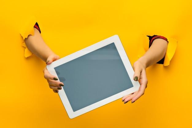 Les mains des adolescentes à l'aide de tablet pc avec écran noir, à travers un papier jaune déchiré, isolé