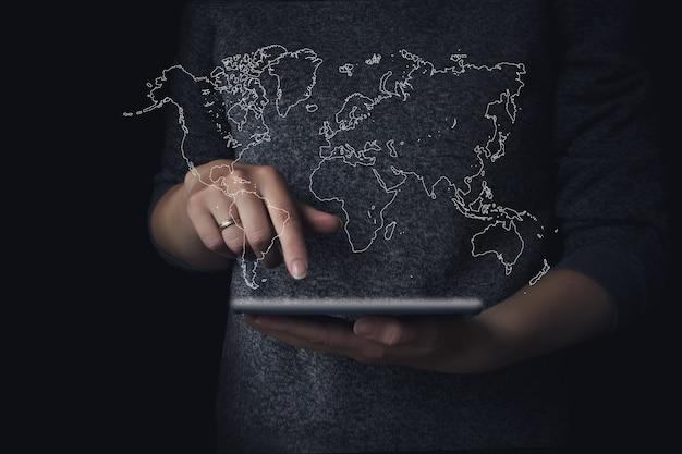 Mains adolescentes à l'aide d'une tablette avec carte du monde hologramme.