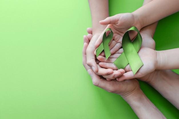 Mains d'adulte et enfant tenant un ruban vert lime sur fond vert