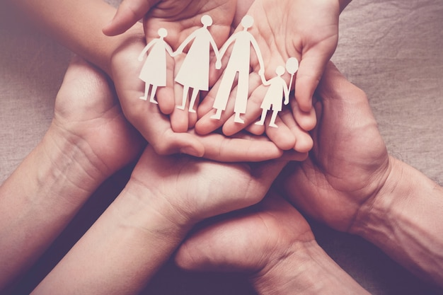 Mains d'adulte et d'enfants tenant une découpe familiale en papier, maison familiale,