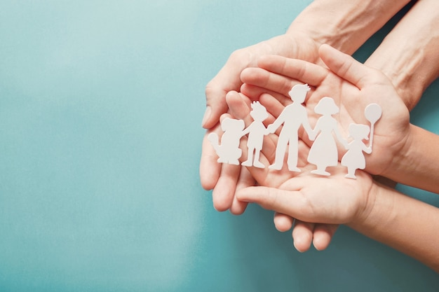Mains adultes et enfants tenant la découpe de la famille de papier, maison familiale, adoption, placement familial.