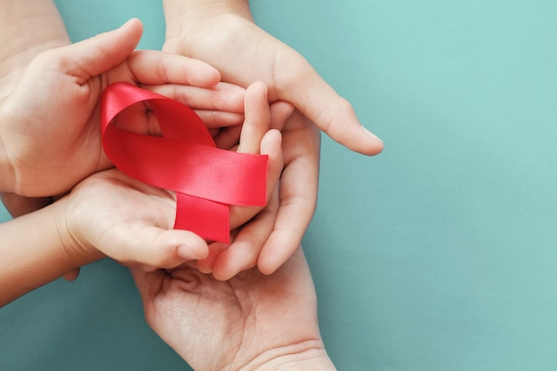 Mains adultes et enfants tenant le ruban rouge sur fond rouge, concept de sensibilisation au vih, journée mondiale du sida, journée mondiale de l'hypertension