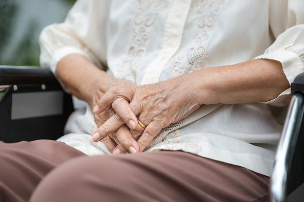 Les mains âgées sur un fauteuil roulant.