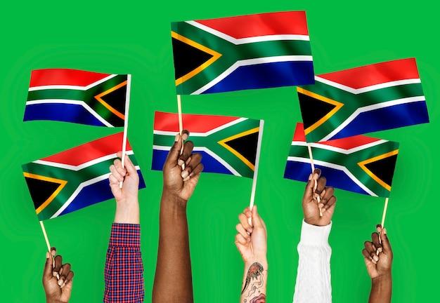 Mains agitant des drapeaux d'afrique du sud
