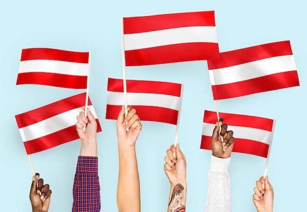 Mains agitant des drapeaux de l'autriche
