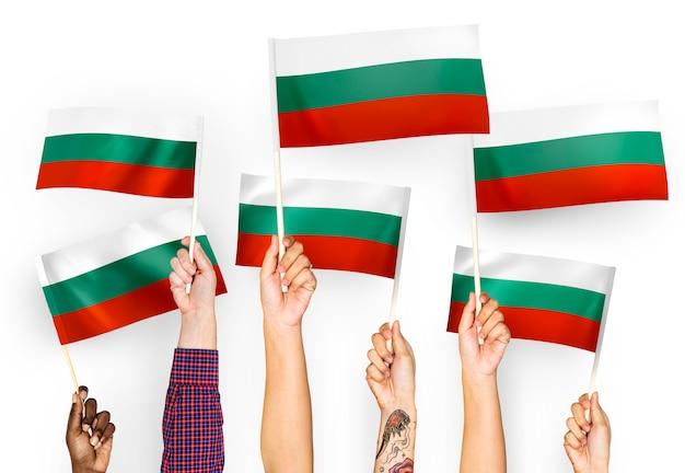 Mains agitant des drapeaux de la bulgarie