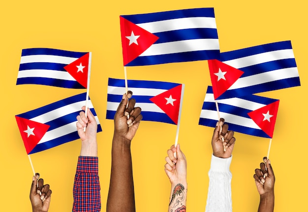 Mains agitant des drapeaux de cuba