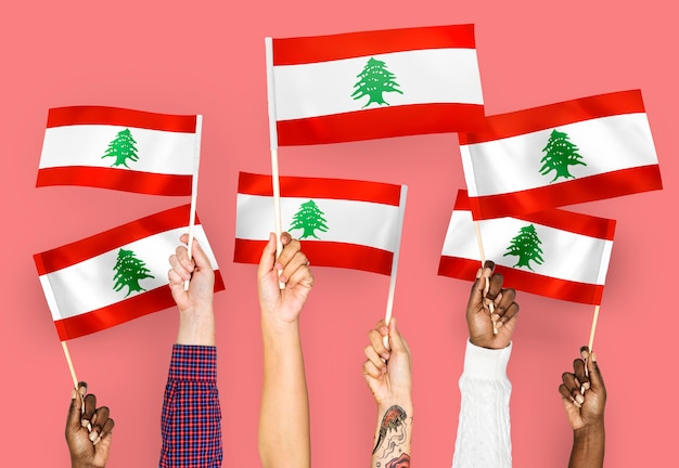 Mains agitant des drapeaux du liban