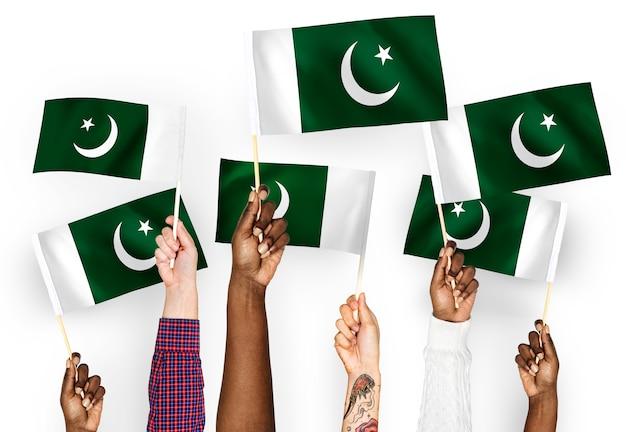 Mains agitant des drapeaux du pakistan