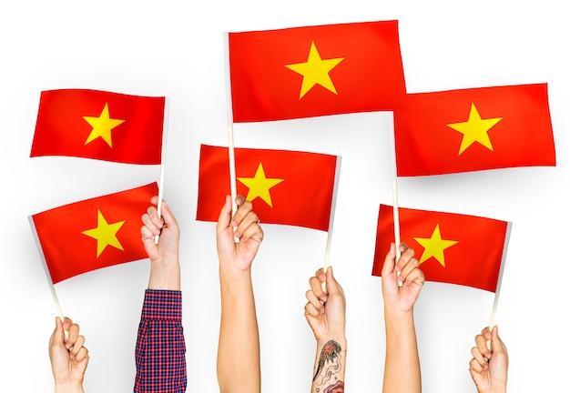 Mains agitant des drapeaux du vietnam