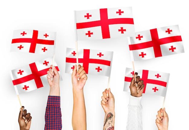 Mains agitant des drapeaux de géorgie