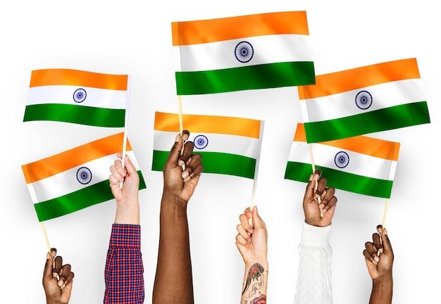Mains agitant des drapeaux de l'inde