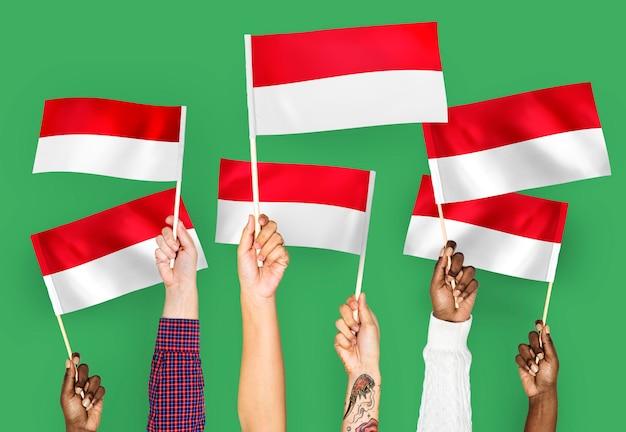 Mains agitant des drapeaux de l'indonésie