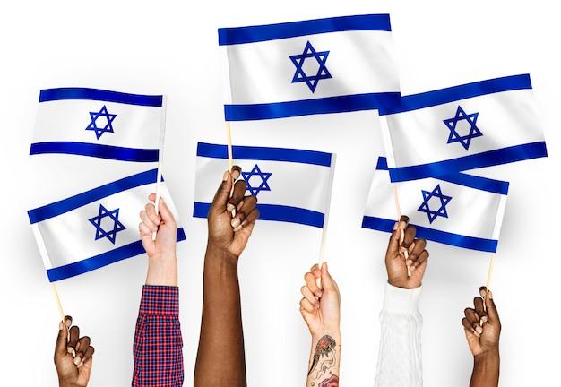 Mains agitant des drapeaux d'israël