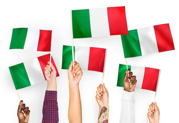 Mains agitant des drapeaux d'italie