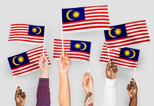 Mains agitant des drapeaux de malaisie