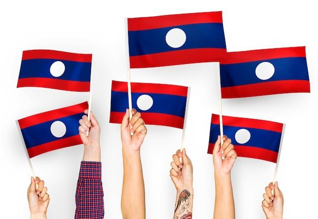 Mains agitant des drapeaux de la république démocratique populaire lao