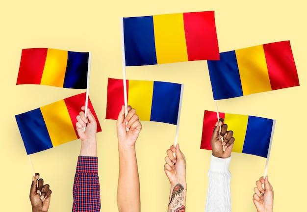 Mains agitant des drapeaux de la roumanie