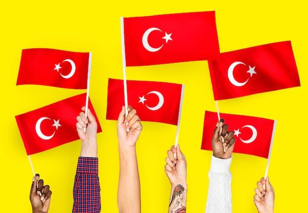 Mains agitant des drapeaux de la turquie
