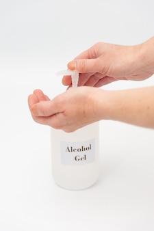 Mains à l'aide de gel d'alcool pour se protéger contre le coronavirus isolé sur fond blanc