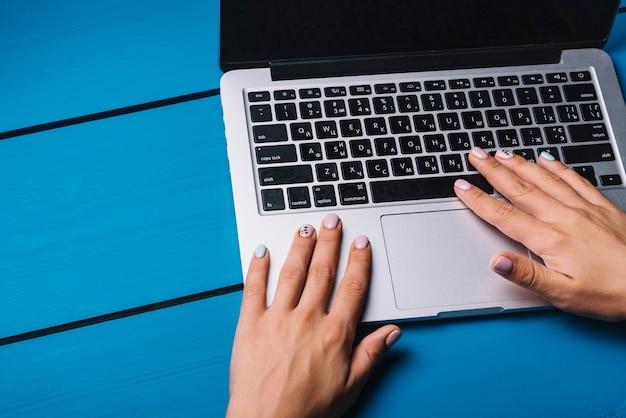 Mains à l'aide d'un ordinateur portable sur le bureau bleu