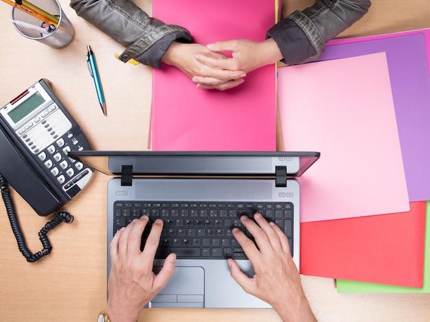 Mains à l'aide d'un ordinateur portable sur le bureau plein de papiers colorés