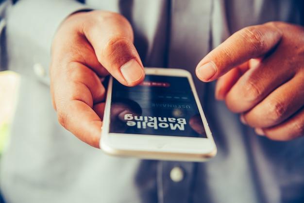 Mains à l'aide de services bancaires mobiles sur téléphone intelligent