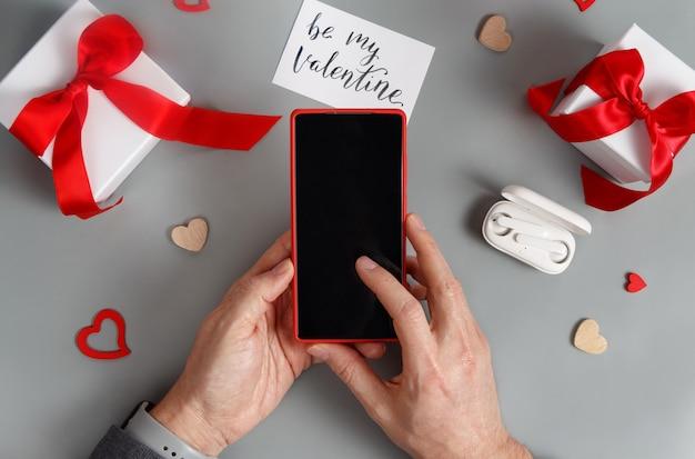 Mains à l'aide de smartphone près de coffrets cadeaux et coeurs sur la vue de dessus de table gris