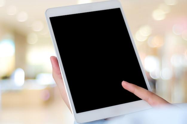 Mains à l'aide de tablette numérique avec écran blanc sur fond flou, pour maquette ba modèle